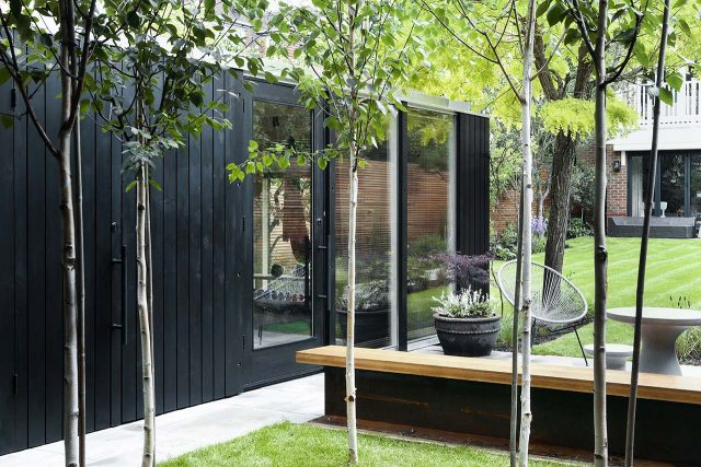 Modular garden room in black cladding adjacent to a seating area