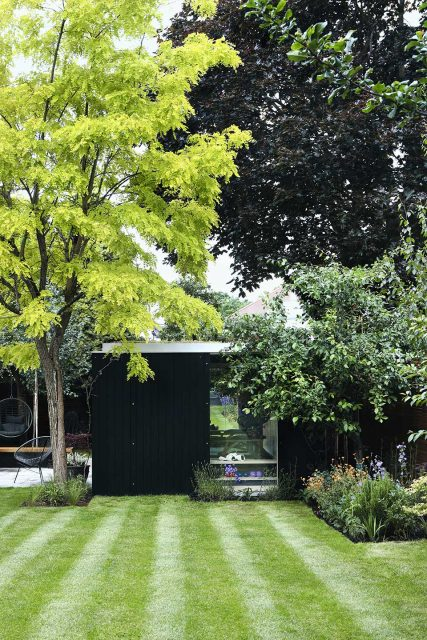 Black Modular garden room position at the end of a garden